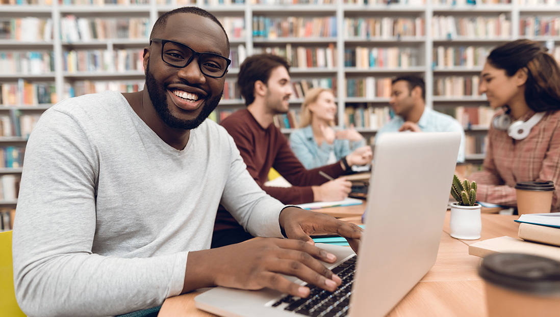 a black student with a laptop in the library.
